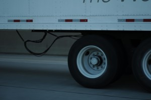 A close up of a tractor trailer as it speeds down a road. The bottom of the truck and two tires are shown.