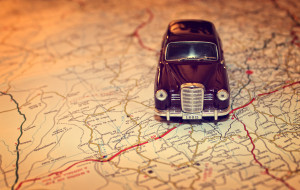 Hit the road - Travel concept with vintage miniature car on road map